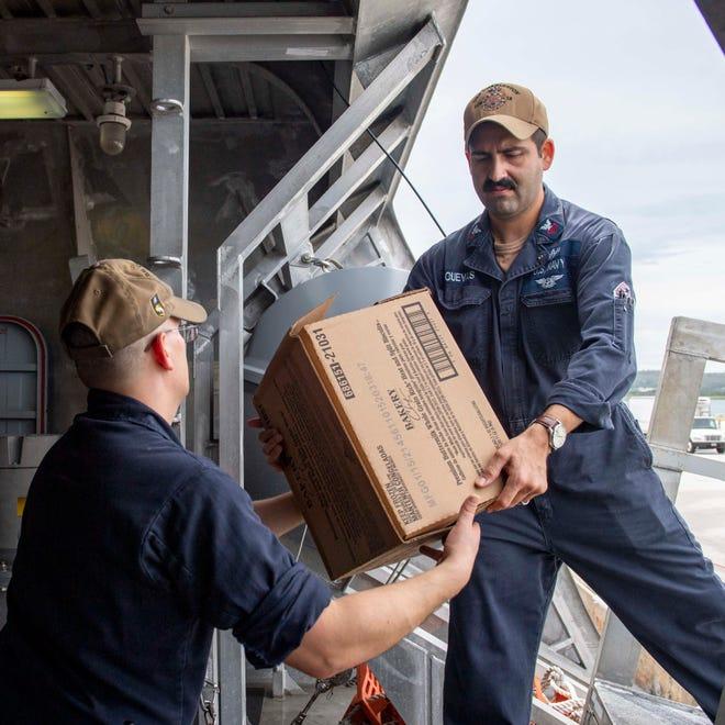Operations Specialist 1st Class Patrick Lloyd, left, of Ravenna, and Operations Specialist 1st Class Luis Cuevas, of San Diego, pass storage aboard the USS Charleston in Apra Harbor in Guam.
