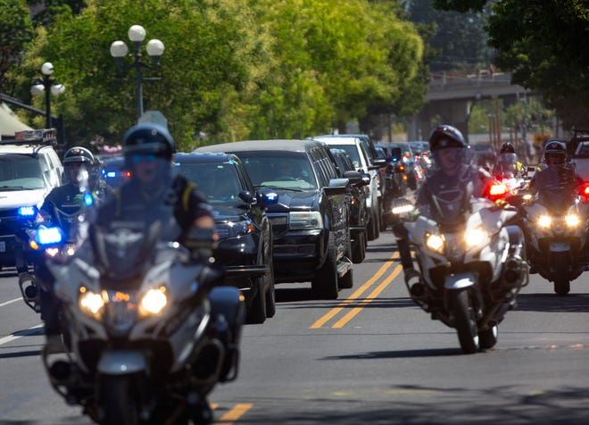 Police vehicles escort a procession including family members down 5th Avenue in Eugene past the Lane County Jail in honor of Deputy Courtney Couch, a deputy with the Lane County Sheriff's Office who accidentally drowned while attempting to help a young child at Foster Reservoir last month.
