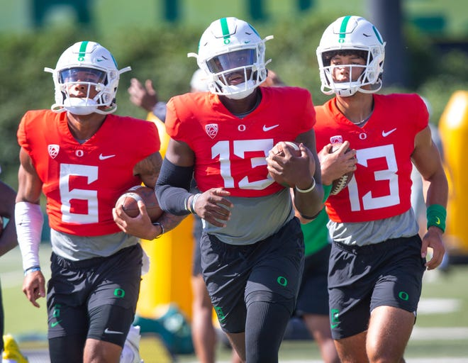 Oregon quarterbacks Robby Ashford, left, Anthony Brown and Ty Thompson work out with the Ducks during fall camp.