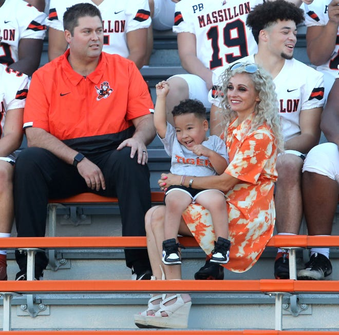Massillon football honorary captain Zaren Berry, center, brother of junior football player Zahnii Berry, gets excited prior to their team photo in Massillon on Aug. 3. Zaren was being held by Becca Moore, right, wife of head coach Nate Moore, left.