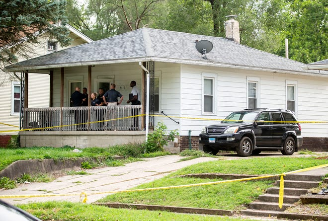 Springfield Police investigators gather Tuesday on the front porch of a residence in the 2500 block of South 10th Street before entering as they work on the day after a shooting with multiple victims in Springfield.