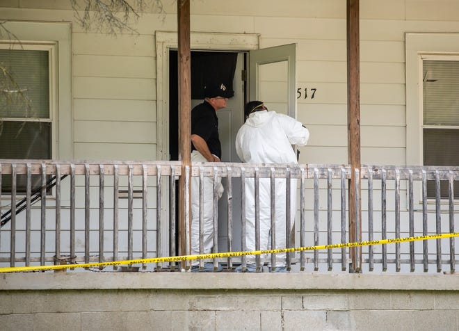 Springfield Police Crime Scene Investigators look over the front door of a residence Tuesday in the 2500 block of South 10th Street as they work the day after three victims were found shot and dead there. [Justin L. Fowler/The State Journal-Register]
