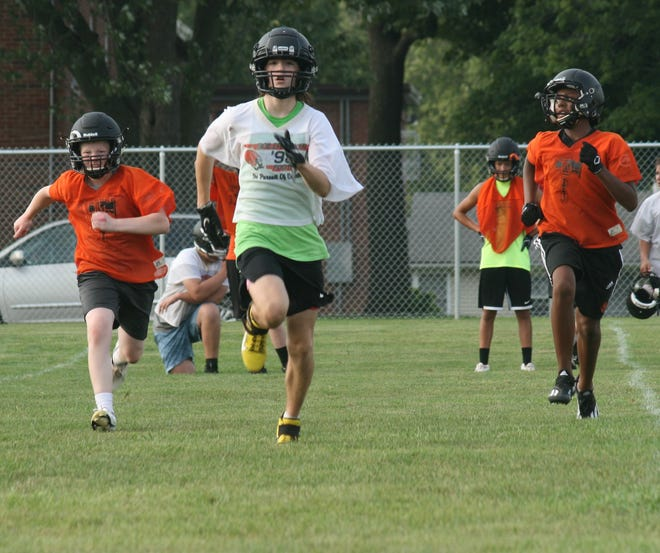 Members of the Kewanee High School Boilermaker football team battled hot, humid weather Monday as they started practicing without contact to mark the start of the Illinois football season. Under new state guidelines, athletes who compete outdoors don't have to wear masks while they are competing.