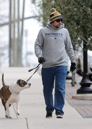 Jon-Erik Tryggestad braves the cooler temperatures while walking his dog George on the sidewalk along Red Cross Street in Wilmington, N.C., on Monday, February 16, 2015.