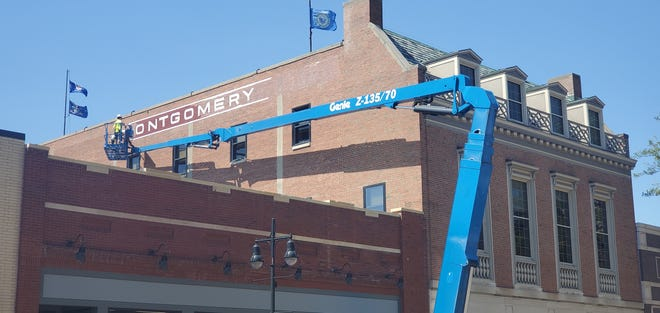 """Crew members from Upper Hand Signs, out of Fargo, paint """"Montgomery's,"""" on Dacotah Bank in downtown Aberdeen. The project is also done by Signs of the Times, also out of Fargo, and is an offshoot of the 2018 Leadership Aberdeen. The sign is expected to be completed on Friday, Aug. 13."""