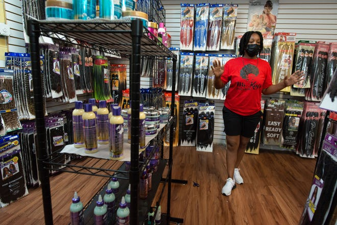 Kelana Boykin, owner of Ms. Key's Beauty Supplies, at 400 S.E. Lake St., walks through her store Tuesday while showing off the selection of products she has in stock.
