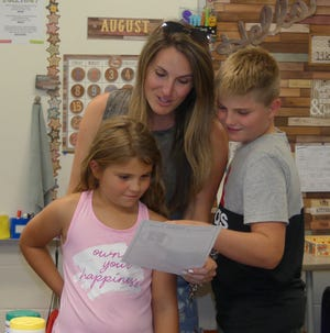 The Springer family reads a welcome letter from Throop Elementary third grade teacher Sharon Perkins during Throop's Meet and Greet on Aug. 3. Pictured are: in front, third grader Feenyx Springer; and back row, Holly, left, and Kutter Springer.