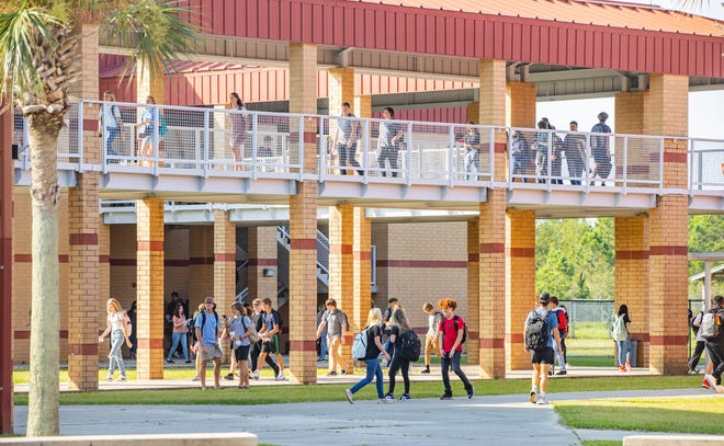 Students at Arnold High School head to their first classes after leaving home room on Aug. 10. A student was arrested on Monday after allegedly helping organize a bomb threat at the school.