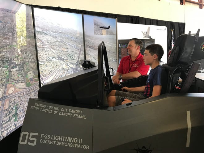 Angelo Dodroe, 13, of Fort Smith tries out an F-35 simulator at TAC Air in the Fort Smith Regional Airport on Tuesday, Aug. 10, 2021, with Cody Blake of Lockheed Martin.
