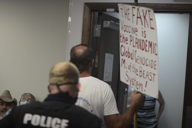 Police escort seven anti-mask protesters from the Black Mountain Town Council meeting on Monday, Aug. 9, 2021.