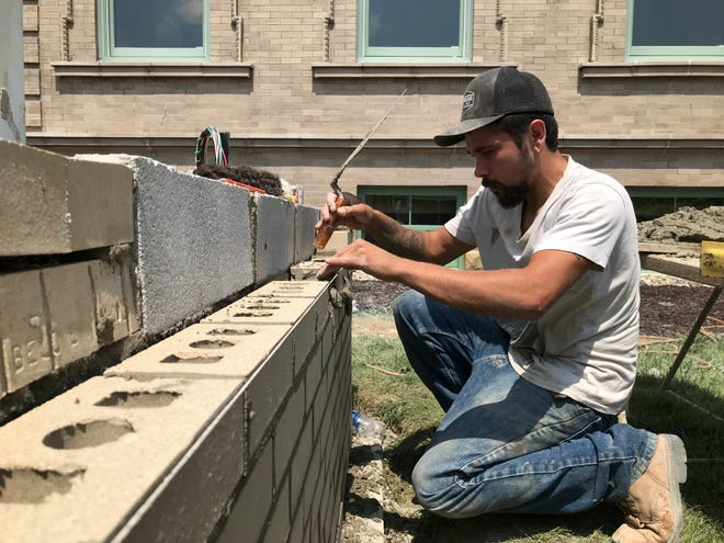 Seth Norris of Grimm Masonry and Concrete sets another brick for the new sign at the Bucyrus Public Library.