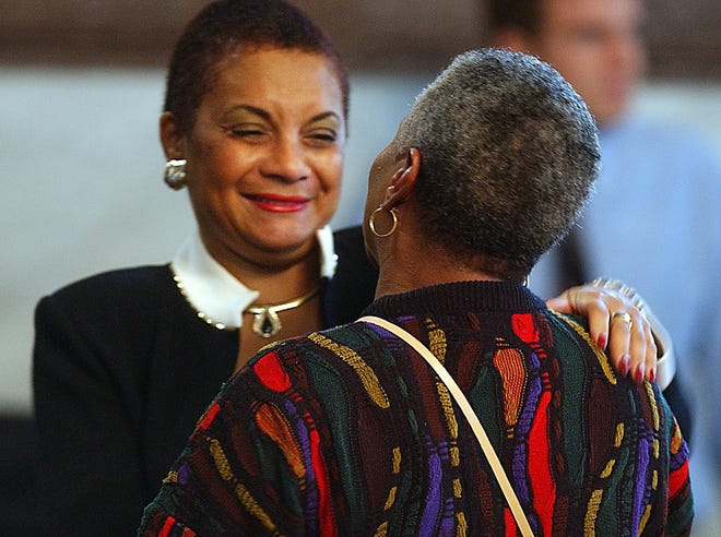 Before her last Cincinnati city council meeting in 2003, outgoing council member Minette Cooper gets a hug from Patricia Carson at City Hall Wednesday afternoon. Carson's son Andre Jones was killed climbing a fence at Woodward High School in January 1999. Cooper helped to get the fence fixed and helped Carson through the ordeal.