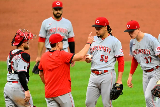Aug 9, 2021; Cleveland, Ohio, USA; Cincinnati Reds starting pitcher Luis Castillo (58) looks on as manager David Bell (25) signals to the bullpen during a pitching change in the fourth inning against the Cleveland Indians at Progressive Field. Mandatory Credit: David Richard-USA TODAY Sports