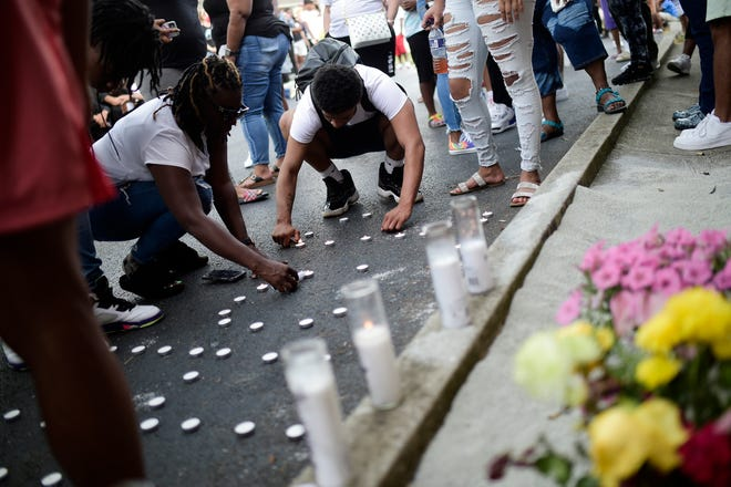People light candles during a vigil for Johnkelian Mathis in Lonsdale Homes in Knoxville, Tenn. on Monday, Aug. 9, 2021. Mathis, a 17-year-old Austin-East Magnet High School student, was shot and killed early Sunday morning.