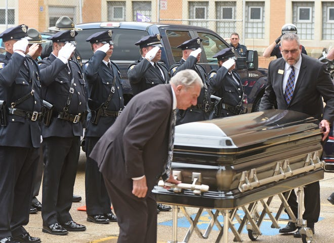 The casket of Joe Wendling is saluted by members of the Mansfield Police Department on Tuesday morning.