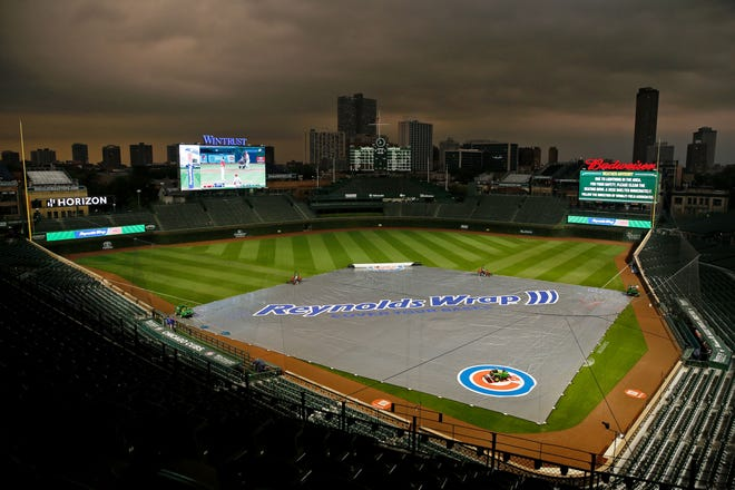 Storm clouds fill the Chicago sky during a rain delay before the game between the Cubs and Brewers at Wrigley Field. The game was rained out and rescheduled as the front end of a split doubleheader Tuesday.