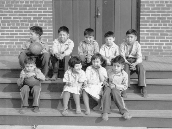 This photo, from around 1935, shows a group of children sitting on the steps of the Indian school at Tomah, according to the Wisconsin Historical Society.