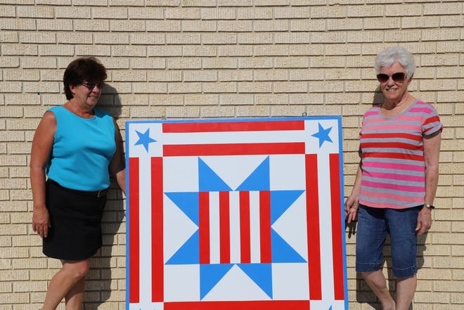 "Joanna Farris and Virginia Cornett pose the Bob Davis Veterans Center's recently donated quilt block titled #5-27 ""A Salute to Veterans."""