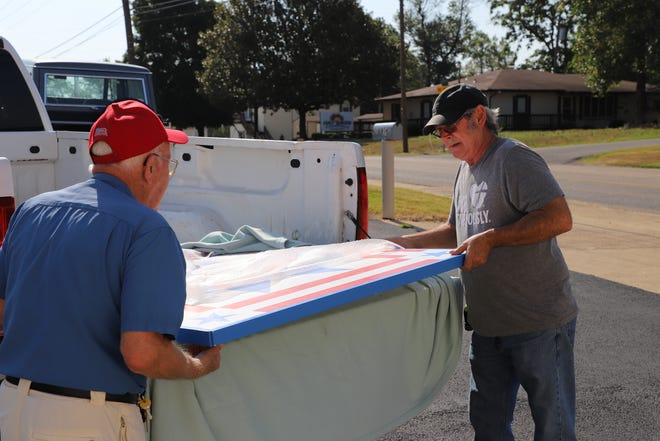 David Farris (right) and Jack Cornett (left) unload The Bob Davis Veterans Center's quilt block. The Bob Davis Center will feature the Baxter County Quilt Trail's 27th quilt block.