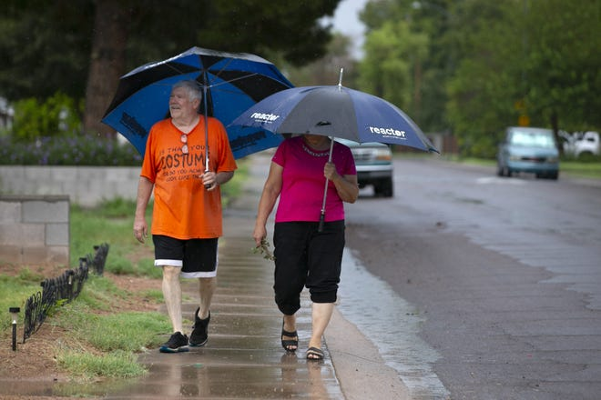Paul and Kathy Yakaitis go for a walk in the rain in Mesa on Aug. 10, 2021.
