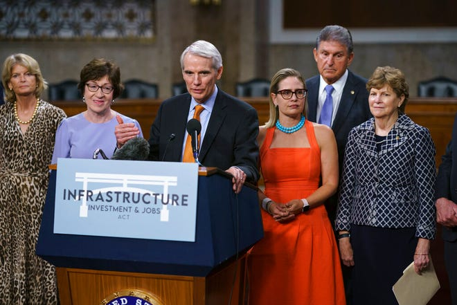 FILE - In this July 28, 2021, file photo the bipartisan group of Senate negotiators, from left, Sen. Lisa Murkowski, R-Alaska, Sen. Susan Collins, R-Maine, Sen. Rob Portman, R-Ohio, Sen. Kyrsten Sinema, D-Ariz., Sen. Joe Manchin, D-W.Va., and Sen. Jeanne Shaheen, D-N.H., speak to reporters just after a vote to start work on a nearly $1 trillion bipartisan infrastructure package, at the Capitol in Washington. Senators are convening for a rare weekend session on the bipartisan infrastructure bill as they edge toward a vote, Saturday, Aug. 7, 2021. (AP Photo/J. Scott Applewhite, File)
