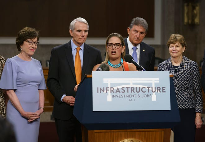 Sen. Kyrsten Sinema, D-Ariz., (center) joined from left by, Sen. Susan Collins, R-Maine, Sen. Rob Portman, R-Ohio, Sen. Joe Manchin, D-W.Va., and Sen. Jeanne Shaheen, D-N.H., speaks to reporters just after a vote to start work on a nearly $1 trillion bipartisan infrastructure package, at the Capitol in Washington on July 28, 2021.
