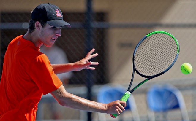 Nate James returns a shot during a doubles tennis match for Central against Lubbock-Cooper on Tuesday, Aug. 10, 2021.