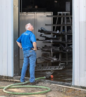 Mark Hellwig looks at damage from a two-alarm shop fire Tuesday, August 10, 2021 at Hellwig Products on Avenue 296 north of Farmersville. The family owned business started 1946.