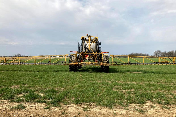 Farmer Rick Clifton drives a spray tractor across one of his fields, applying herbicide to cover crops that occupied the ground during fall and winter in Orient, Ohio, on April 5, 2021. Clifton grows cereal rye and rapeseed to prevent erosion and make the ground healthier for his corn, soybean and wheat cash crops. Cover crops store carbon in the soil, keeping the greenhouse gas out of the atmosphere.