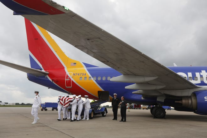 The casket bearing the remains of Seaman 1st Class Russell C. Roach is carried from a plane at Columbus John Glenn International Airport on Monday. Roach was then escorted to Zanesville in preparation for his funeral on Wednesday.