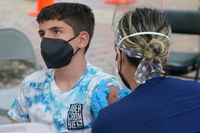 Andres Veloso, 12, gets the first dose of the Pfizer COVID-19 vaccine, Monday, Aug. 9, 2021, in Miami. Florida is reporting a surge of COVID-19 cases caused by the highly contagious delta variant. (AP Photo/Marta Lavandier)