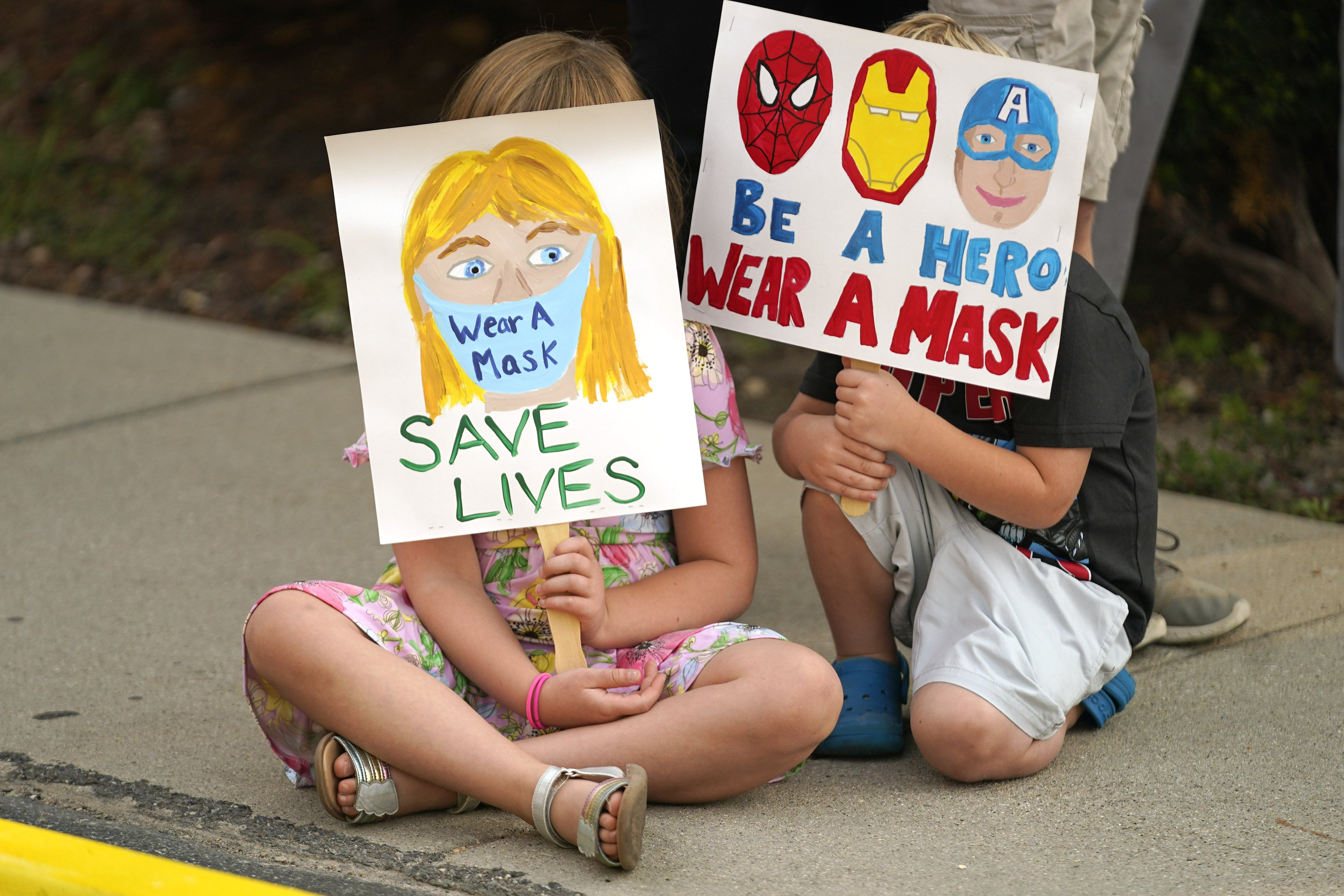 Lucie Phillips, 6, and her brother David Phillips, 3, join parents and students during a rally at the Utah State School Board Office calling for a mask mandate on Aug. 6. [AP PHOTO/RICK BOWMER]