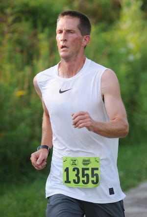 Gary Pate crosses the finish line with a time of 22:51.77 to claim first place in the 2021 Greater Alliance Carnation Festival Trail Run Tuesday, August 10, 2021, at the Iron Horse Trail.