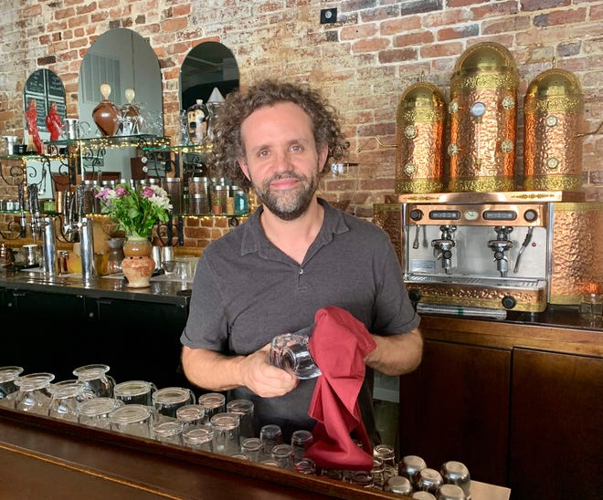Owner Eric Kinlaw cleans a glass at his new coffee bar in The Bee's Knees in downtown Augusta. He says the changes he has made in the business reflect more of who he is and what he values.