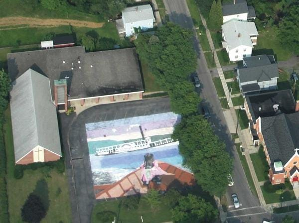 This photo of the 2009 painting in the Penn Yan First Presbyterian parking lot was taken by 13-year-old Josh Baxter from a plane flown by his father, Eric. Dozens of artists worked together July 25, 2009 at the Penn Yan Presbyterian Church to complete a giant painting depicting a photograph from the early 1900s. This year's painting, to be executed under the direction of Bob Gillespie Aug. 30-31, will feature ice boats on Keuka Lake.