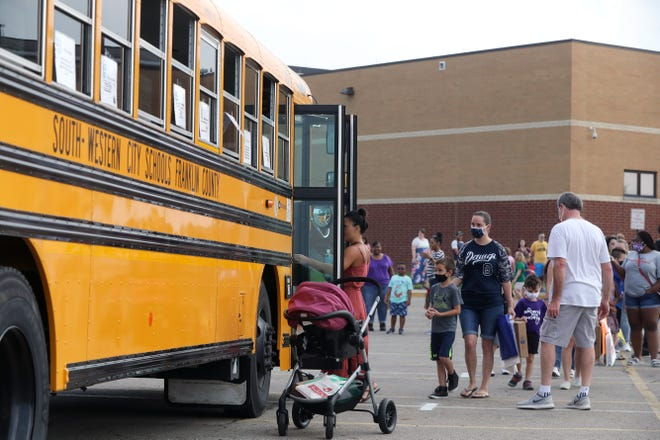 Parents and students line up to board a school bus as part of the first-time bus rider program at the South-Western City School District's kindergarten open house Aug. 7 at Central Crossing High School in Grove City.
