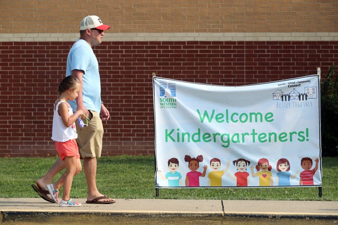 Kraig Miller of Grove City walks his daughter, Sophia, 5, to meet her teacher and collect school materials during the South-Western City School District's kindergarten open house Aug. 7 at Central Crossing High School in Grove City.