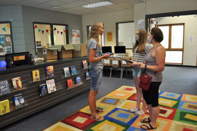 Adelaide McGuire, 13, an eighth-grader at Hilliard Weaver Middle School, picks up her district-issued iPad Aug. 1, from Heather Conrad (left), a supplemental-services teacher for Hilliard City Schools. McGuire is with her mother, Anne Lohrmann (right).