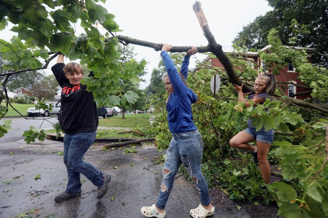 Devin Reynolds and her daughters, Alexis, 13, and Shia, 16, remove broken tree limbs from a large maple tree that was blown over Wednesday following a strong thunderstorm that blew through the area, toppling trees near the intersection of Franklin and Ninth streets in Burlington. The group moved on once workers with Walker Outdoor Services, which was contracted by the city, showed up to remove the downed tree.