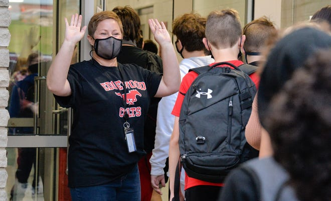 Teacher Rebecca Guest-Scott greets students arriving off the bus for their first day of school Wednesday morning at Edgewood Junior High School in Ellettsville.