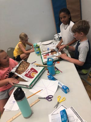 Monroe Family YMCA Summer Day campers participate in a STEM project. They are building solar cookers. Courtesy photo