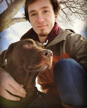 Austin Smith and his chocolate labrador retriever, Reese.