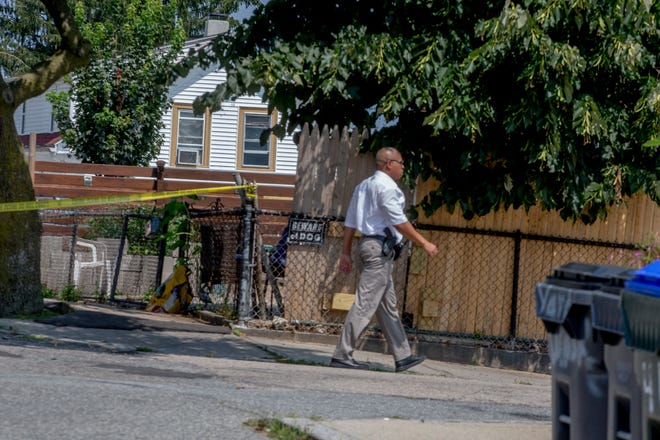 A Providence officer is outside a home on Sears Avenue, where Luis Roman, who is suspected of shooting at a Providence police officer, was arrested.