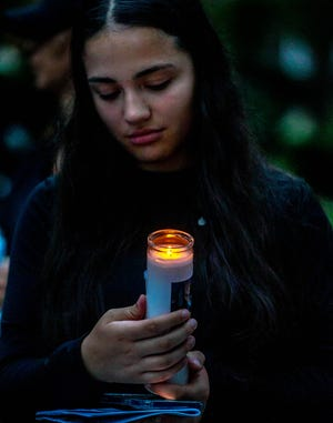 Jaliyah Joseph of Black Lives Matter RI PAC holds her candle during the vigil.