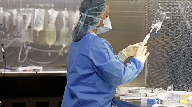 A pharmacy technician prepares syringes.