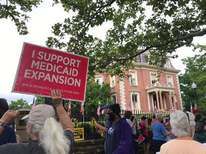 Demonstrators stand outside of the Governor's Mansion in Jefferson City on July 1, 2021 and hold signs urging Gov. Mike Parson to fund voter-approved Medicaid expansion (Photo by Tessa Weinberg/Missouri Independent