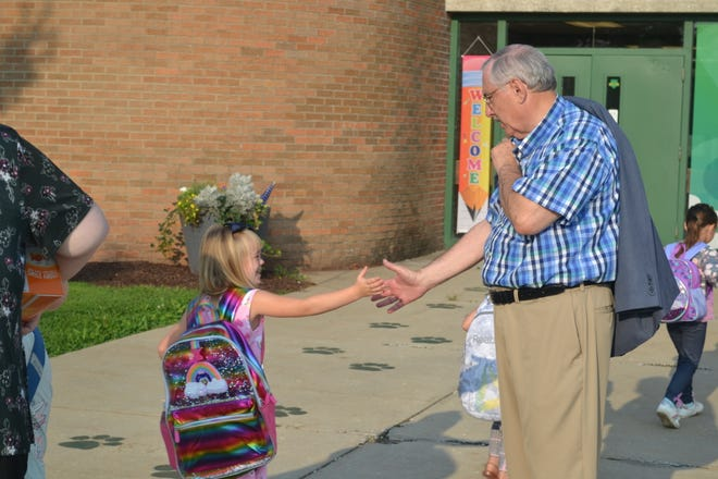 A child enthusiastically high-fives Dr. Roberson at Paragon Elementary.