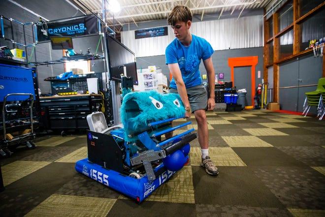 Weston Markham demonstrates a robot he helped design at E3 Robotics in Elkhart.