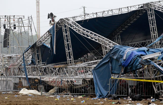 In this Sunday, Aug. 14, 2011, file photo, the Indiana State Police and authorities survey the collapsed rigging and Sugarland stage on the infield at the Indiana State Fair in Indianapolis.