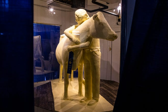 """The 2021 Butter Cow by sculptor Sarah Pratt unveiled Wednesday in the Dairy Building at the Illinois State Fairgrounds marks the 100th anniversary of the Butter Cow at the Illinois State Fair in Springfield. The theme of this year's Butter Cow is """"Embracing Tradition"""" and features a young exhibitor embracing the cow along with 13 hearts hidden throughout representing the 13 essential nutrients found naturally in milk. [Justin L. Fowler/The State Journal-Register]"""